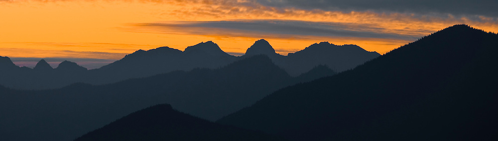 Post sunset alpenglow lights the sky over the northeastern region of the Olympic Mountains in Washington, USA. panorama