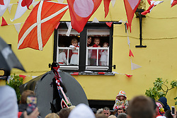© Licensed to London News Pictures. 01/05/2017 May Day celebrations in Padstow Cornwall. Kids look down from the Golden Lion Pub at the Red Oss.The Blue Oss and the Red Osds lead the traditional May Day celebrations around the historic harbour of Padstow in Cornwall.<br /> Despite the rain large crowds attended the annual event.Photo credit : MARK HEMSWORTH/LNP