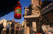 A plastic drinks bottle hangs from a food kiosk opposite ancient Roman archaeology in the Italian capital, on 3rd November 1999, in Rome, Italy.