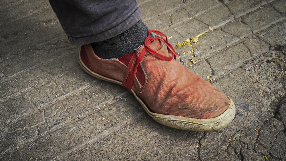 A Honduran migrant tied his shoe with string to stop the sole falling off. In southern Mexico he had to walk two weeks, day and night with little sleep in extreme temperatures, then he was chased by migration police through rough terrain for hours and his shoes fell apart.