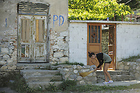 Woman in the Albanian village clean the step and surroundings every morning. Lesser Lake Prespa, Lake Prespa National Park, Albania June 2009