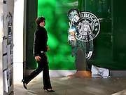 © Licensed to London News Pictures. 02/11/2011. London, UK. A woman in a suit walks past a Starbuck logo with a figure added. Occupy London protesters outside St Paul's Cathedral today, 2nd November 2011.  Photo credit : Stephen Simpson/LNP