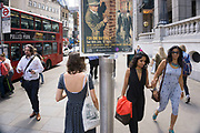 Sinister poster advertising for a club night, looks over the shoulders of passing people near to Liverpool Street station on Bishopsgate. London, UK. The character on the poster is that of a 1940s secret agent, private investigator or spy looking at his target.