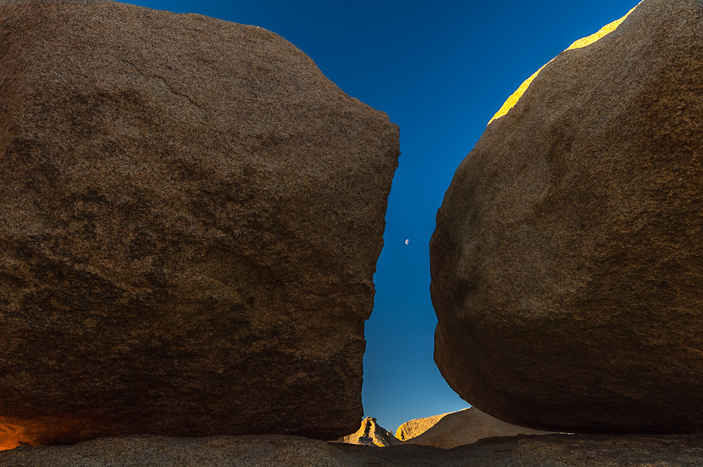 Granite boulders frame a half moon, morning light, March, Joshua Tree National Park, San Bernardino County, California, USA.