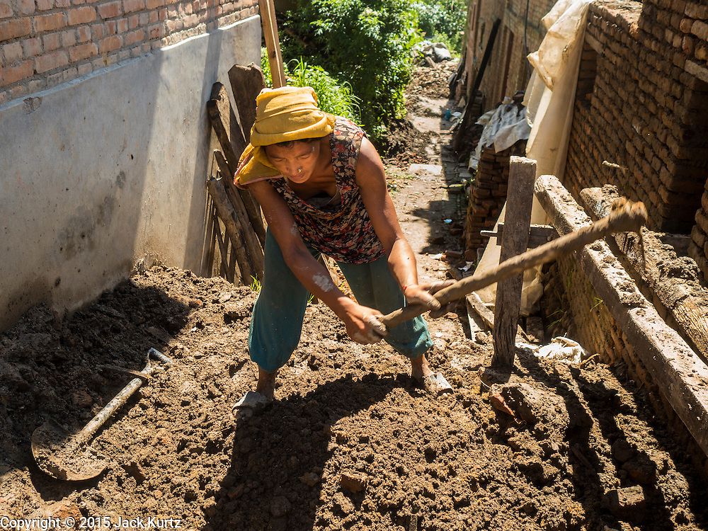 03 AUGUST 2015 - SANKHU, NEPAL:  A woman digs up mud to be used as mortar in the repair of a home destroyed in the earthquake in Sankhu, a community about 90 minutes from central Kathmandu. The Nepal Earthquake on April 25, 2015, (also known as the Gorkha earthquake) killed more than 9,000 people and injured more than 23,000. It had a magnitude of 7.8. The epicenter was east of the district of Lamjung, and its hypocenter was at a depth of approximately 15km (9.3mi). It was the worst natural disaster to strike Nepal since the 1934 Nepal–Bihar earthquake. The earthquake triggered an avalanche on Mount Everest, killing at least 19. The earthquake also set off an avalanche in the Langtang valley, where 250 people were reported missing. Hundreds of thousands of people were made homeless with entire villages flattened across many districts of the country. Centuries-old buildings were destroyed at UNESCO World Heritage sites in the Kathmandu Valley, including some at the Kathmandu Durbar Square, the Patan Durbar Squar, the Bhaktapur Durbar Square, the Changu Narayan Temple and the Swayambhunath Stupa. Geophysicists and other experts had warned for decades that Nepal was vulnerable to a deadly earthquake, particularly because of its geology, urbanization, and architecture.    PHOTO BY JACK KURTZ