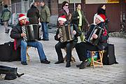 Uliczni akordeoniści grający przed Kościołem Mariackim w okresie przedświątecznym.