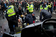 See through a stationary bus window, environmental protesters chain themselves together and glue body parts to the road in Fleet Street on the 11th and final day of protests, road-blockages and arrests across London by the climate change campaign Extinction Rebellion, on 25th April 2019, in London, England.