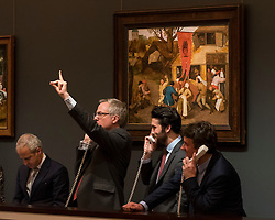 "© Licensed to London News Pictures. 07/12/2016. London, UK. Sotheby's staff make bids on behalf of telephone clients in front of ""A Village Kermesse"" by Circle of Pieter Bruegel the Elder sold for a hammer price of GBP125k (est. GBP 80-120k),    at the Old Masters Evening Sale at Sotheby's in New Bond Street. Photo credit : Stephen Chung/LNP"