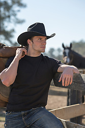 portrait of a hot cowboy in a black tee shirt on a ranch cowboy leaning on a wooden fence