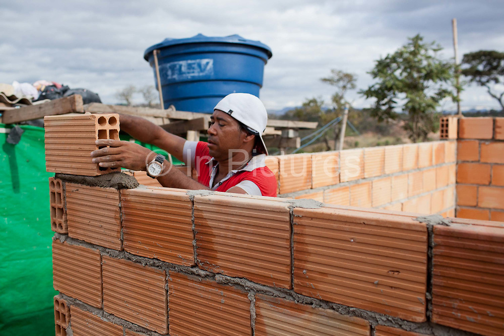 Man building a house. Isidoro occupation in Belo Horizonte, Minas Gerais in a large  amount of land that was occupied by the MLB, a Brazilian workers social movement, it faced eviction in July / August 2014. (photo by Phil Clarke Hill/In Pictures via Getty Images)