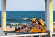 Spring Lake, NJ USA -- 8/29/2015 A romantic couple sits together on the boardwalk, watching the ocean in the late afternoon.