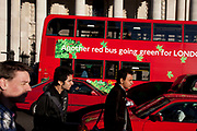 Red cars and a Red London bus in the centre of town. People pass while the bus advertises for a greener London. Hardly the impression this scene depicts.
