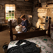 Director Nancy Kaiser sits in a rocking chair as a period dress lays on the bed in the recreation of the childhood home of Abraham Lincoln at the Lincoln Pioneer Village and Museum in Rockport, Indiana. Nathan Lambrecht/Journal Communications