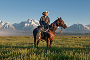A wrangler stopping to count the herd in the morning light with Mt. Moran and the Grand Teton mountain range in the background.