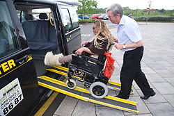Taxi driver helping a young woman with Cerebral Palsy get in to a taxi,