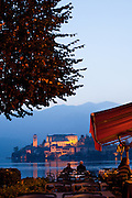 A couple dines lakeside on Lake Orta, with the island monastery of Isola San Giulio in the distance, Orta San Giulio, Piedmont, Italy.
