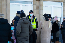 Portobello, Scotland, UK. 24 January 2020. Large numbers of members of the public at Portobello beach and promenade on sunny Sunday afternoon during lockdown. While most people observed social distancing groups of people formed at some of the cafes offering takeaway food and drinks. Police patrols spoke to public sitting down and in groups at cafes to ask them to move on. Pic; Police talk to members of the public gathered outside cafe and ask them to move on. Iain Masterton/Alamy Live News