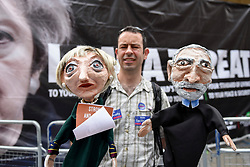 "© Licensed to London News Pictures. 02/06/2017. London, UK. A man carries papier mache puppets depicting Theresa May and Jeremy Corbyn. Demonstrators gather outside the BBC headquarters in protest against the Corporation for not playing the song ""Liar Liar"" by Captain Ska on BBC Radio 1.  Organised by The People's Alliance, people carried signs bearing an image of Prime Minister Theresa May with the words ""Liar Liar"" and ""You Can't Trust Her"" on each side.   Photo credit : Stephen Chung/LNP"