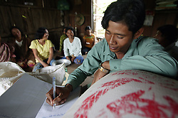 Rice cooperative in Takom village, Battambang, Cambodia. The rice store committee has many members and they introduce villagers to the principles of trading rice to give them security at a much reduced rate than the market offers.<br /> Dy Yong keeps the books for the rice Bank Committee so that everybody can see how it run and maintained.