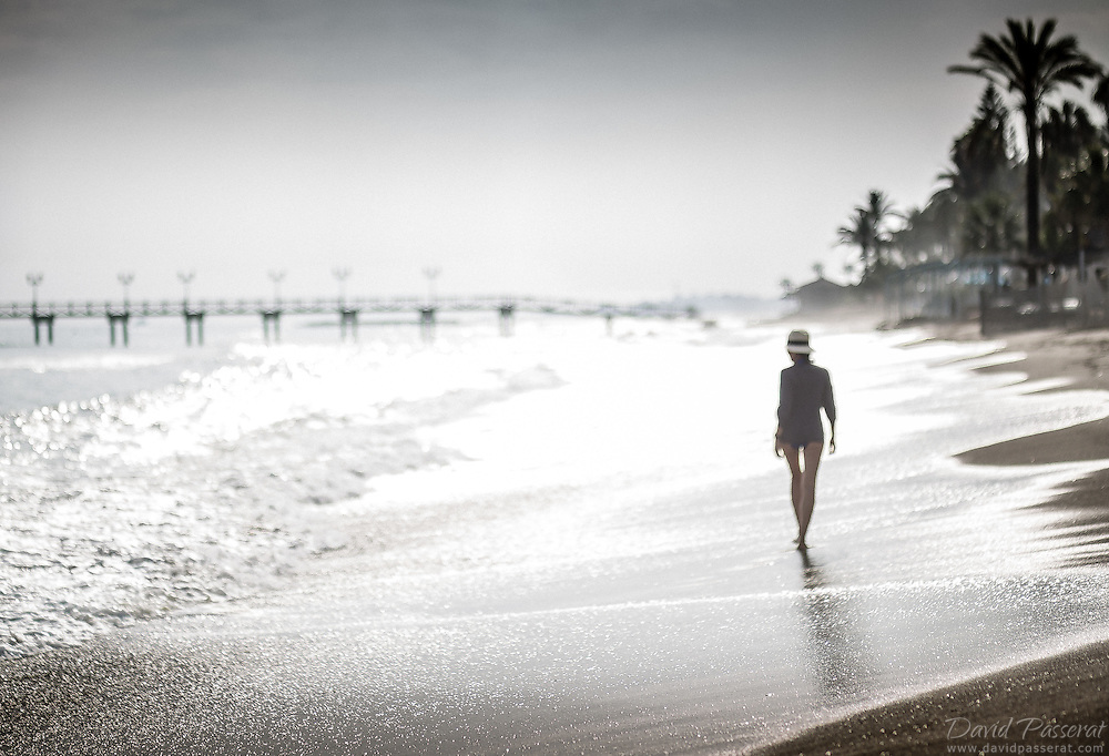 Lens: 85mm, aperture 1.8.<br /> The focus is on the foreground sand and the subject is out of focus. At first I thought I missed the shot but the effect with the hard light of the sun on the sea and the blurred of the subject makes it a original capture.