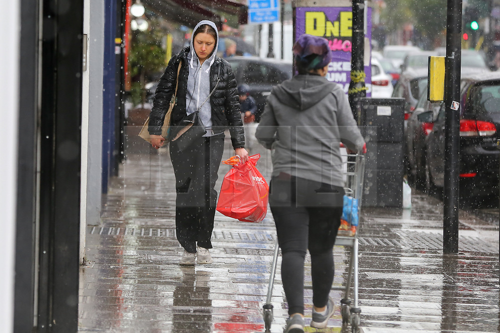 © Licensed to London News Pictures. 02/05/2021. London, UK. People are caught in the rain in north London. Windy and wet weather is forecasted for the bank holiday Monday. <br /> Photo credit: Dinendra Haria/LNP