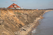 Coastal erosion of soft sandy cliffs at Easton Bavents, near Southwold, Suffolk, England. The lower darker band at the bottom of the cliff is remains of do-it-yourself coastal protection by local resident Peter Boggis, who dumped thousands of tons to try to keep back the sea.