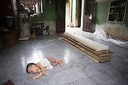 Color film photograph of a small child sleeping on the tiled floor inside a house of Tho Ha Village, a craft village specialized in making rice paper cakes with a history of pottery ware production, Hanoi outskirts, Vietnam, Southeast Asia