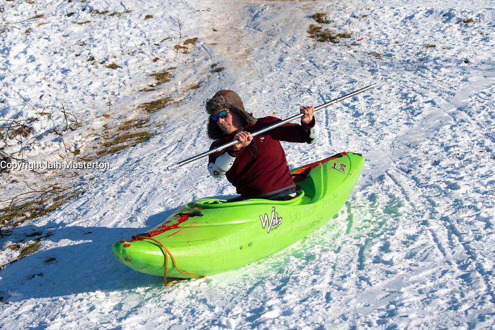 Edinburgh, Scotland, UK. 12 Feb 2021.  As the cold weather continues members of the public are out in Holyrood Park playing sport and making political slogans. Pic; A man in a canoe hurtles down a snow covered hillside at the foot of Arthur's Seat . Iain Masterton/Alamy Live news