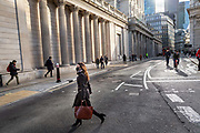 A woman wearing a protective face mask crosses the road in front of the Bank of England in what would normally be the morning rush hour in the City of London on March 17th, 2020. The financial district of the UK is unusually quiet after the government requested people to refrain from all but essential travel and activities yesterday.