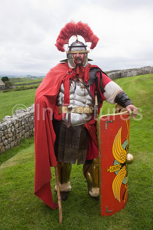Re-enactment soldier at Housesteads Fort on Roman Hadrian's Wall, once the northern frontier of Rome's empire. Hadrian's Wall (Latin: Vallum Aelium) was a stone and timber fortification built by the Roman Empire across the width of what is now northern England. Begun in AD 122, during the rule of emperor Hadrian, it was built as a military fortification though gates through the wall served as customs posts to allow trade and levy taxation. The 4.5m high Wall was 80 Roman miles (73.5 miles, 117km) long and so important was it to secure its length that up to 10% of the Roman army total force were stationed here. Tough walkers generally take 7 days to trek its coast-to-coast length. This Roman soldier enthusiast has dressed up for a Roman day.