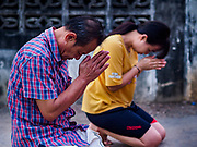 13 JANUARY 2019 - NAKHON PATHOM, THAILAND:  A couple prays after giving alms to the female monks from Wat Songdhammakalyani. The Sangha Supreme Council, Thailand's governing body of Buddhist monks, bans the ordination of female monks, but hundreds of Thai women have gone abroad, mostly to Sri Lanka and India, to be ordained. There are about 270 women monks in Thailand and about 250,000 male monks. There are 7 monks and 6 novices at Wat Songdhammakalyani in Nakhon Pathom. It was the first temple in Thailand to have female monks. The temple opened 60 years ago and has always been a temple of women monks. Women can be ordained as novices in Thailand, but to be ordained as a full monk would require the participation of 10 female monks and 10 male monks, and male monks in Thailand are barred from participating in women's ordination ceremonies.     PHOTO BY JACK KURTZ