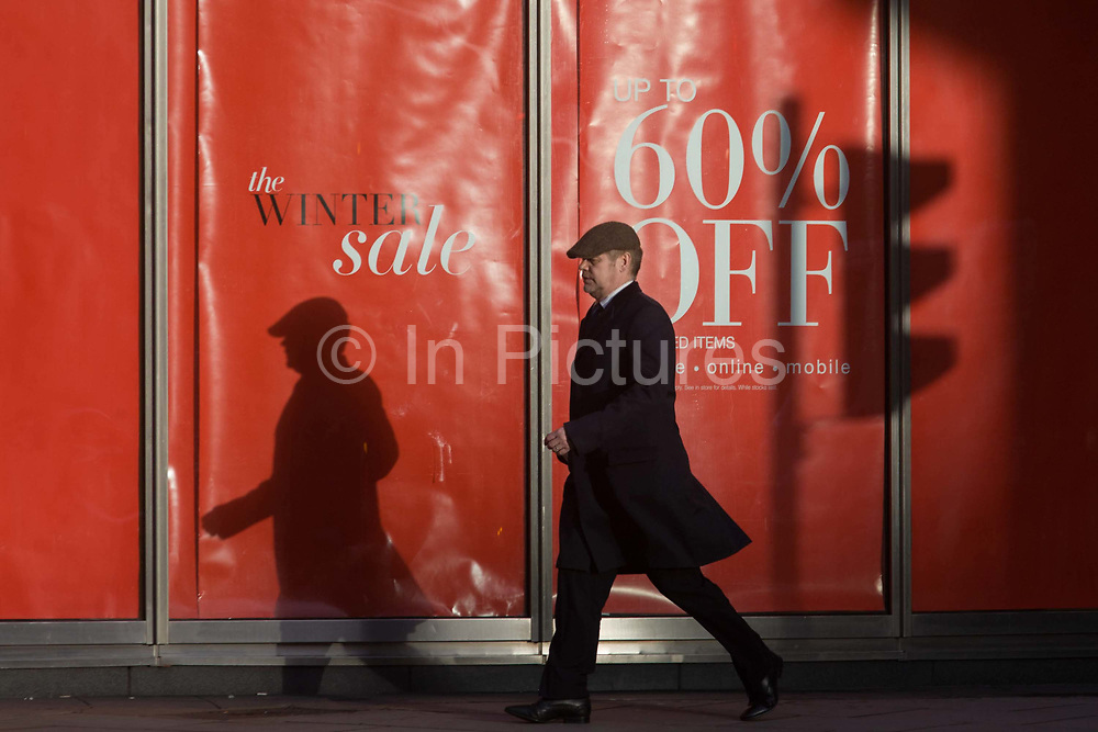 Sale reductions at a branch of UK retailer Marks & Spencer, on Bishopsgate in the City of London. With his own shadow and that of a nearby traffic light, a gentleman consumer wearing a flat cap walks past a banner announcing the new post-Christmas winter sale offering up to 60% reductions on clothing. Marks & Spencer has over the last 129 years grown from a single market stall to become an international multi-channel retailer, now operating in over 50 territories worldwide and employing almost 82,000 people.