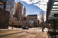 A vehicle crosses an empty intersection of the downtown neighborhood with the recognizable pyramid-shaped pinnacle of Smith Tower (Seattle's first skyscraper) in the background. (April 4, 2020)