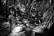 In a remote hilltribe area of Khanh Hoa, a woman sits on the ground and hugs her son. Jungle surrounds the place. Vietnam, Asia