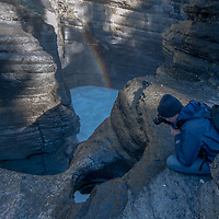 A photographers frames views of Mistaya Canyon, where the large Mistaya River plunges into a narrow slot canyon it has eroded over time.