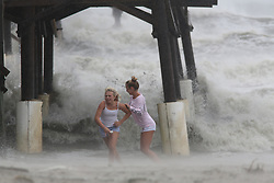 October 8, 2016 - Cocoa Beach, Florida, U.S. - KALEIGH BLACK, 14, left, and AMBER OLSEN, 12, run for cover as a squall with rain and wind pelt them while they explore the Cocoa Beach Pier on Friday after hurricane Matthew passed to the east on Florida's east coast. (Credit Image: © Douglas R. Clifford/Tampa Bay Times via ZUMA Wire)