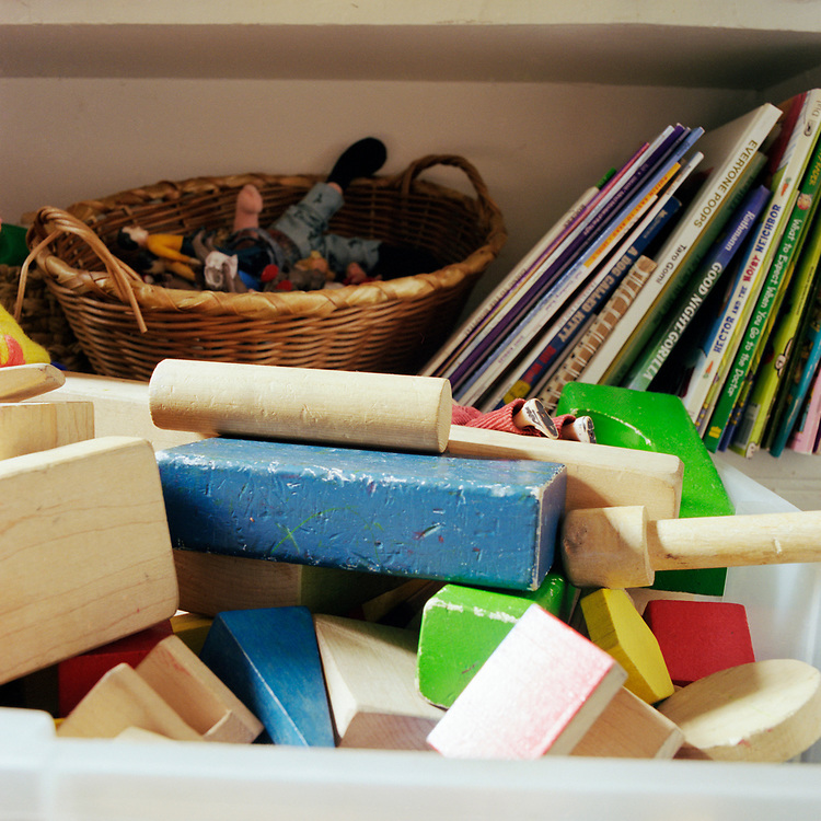 Building blocks in a plastic tub in front of a book shelf of children's books and toys.