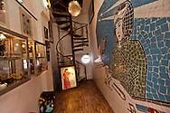 The artfilled narrow entryway of boutique propaganda shop P, with a spiral staircase at the far end, Nha Chung steet, Hanoi, <br /> Vietnam, Southeast Asia