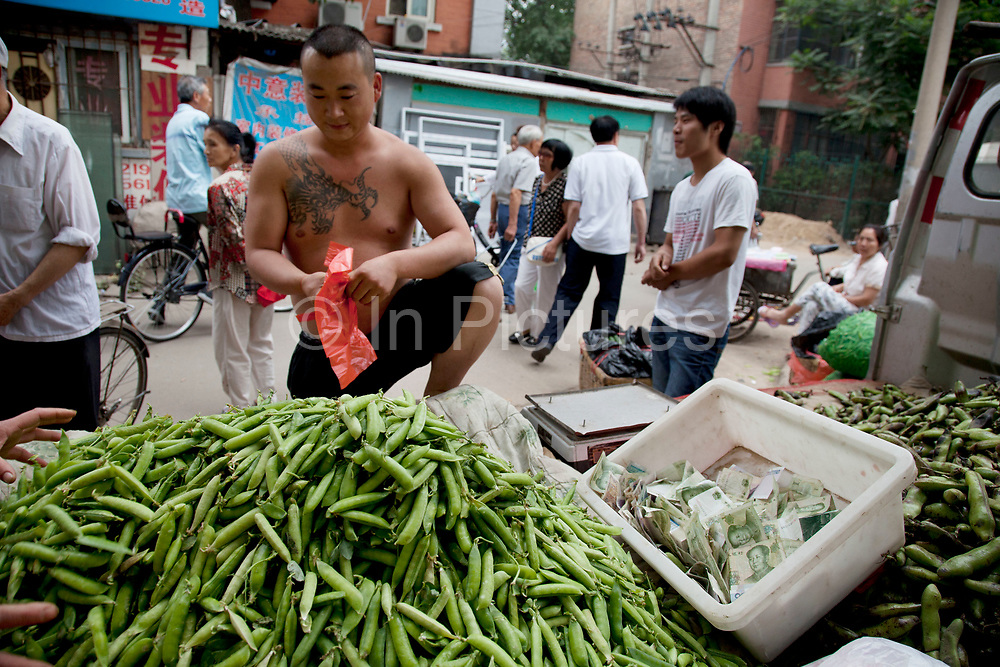 Pea seller. Street market in an old Chinese style area of Fuchengmen, in the Xicheng district of Beijing, China. This neighbourhood, tucked away behind a major road had people selling food in the street as well as in a covered market.