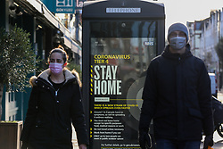 © Licensed to London News Pictures. 02/01/2021. London, UK. A couple wearing protective face coverings in north London walk past the government's 'Coronavirus Tier 4 - Stay Home' publicity campaign poster, after the mutated variant of the SARS-Cov-2 virus continues to spread around the country. The President of the Royal College of Physicians,Professor Andrew Goddard, has warned that COVID-19 infection cases are set to rise in the coming weeks and that NHS staff and healthcare workers are worried about the challenges against the virus over the coming months. Photo credit: Dinendra Haria/LNP
