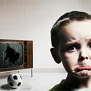 A humorous image depicting a young boy with a worried face as a result to breaking the television whilst playing with his football inside the house. Photographed by Stuart Freeman.