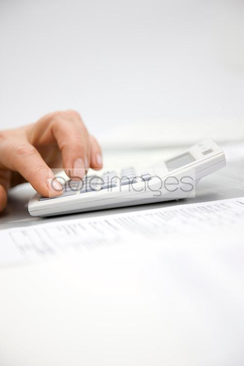 Close up of a woman hand pressing a calculator key