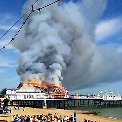 © Licensed to London News Pictures. 30/07/2014. Eastbourne, UK A fire has broken out on Eastbourne Pier this afternoon, 30th July 2014. Firefighters, police, coastguards and lifeboat crews are at the scene after a fire was discovered in a wall panel of an arcade at the front of the Victorian structure. Photo credit : Jack Seale/LNP