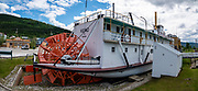 Preserved historic 1922-1951 sternwheel paddle steamer, SS Keno National Historic Site of Canada, at dry dock along the Yukon River in Dawson City, Yukon, Canada. The vessel was built in 1922 in Whitehorse by the British Yukon Navigation Company, a subsidiary of the White Pass and Yukon Route railway company. It mostly transported silver, zinc and lead ore down the Stewart River from mines in the Mayo district to the confluence of the Yukon and Stewart rivers at Stewart City. It was retired from commercial service in 1951 due to the extension and improvement of the Klondike Highway in the years after World War II. About 250 sternwheelers served the Yukon River and its tributaries. Dawson City was the center of the Klondike Gold Rush (1896–99), after which population rapidly declined. Dawson City shrank further during World War II after the Alaska Highway bypassed it 300 miles (480 km) to the south using Whitehorse as a hub. In 1953, Whitehorse replaced Dawson City as Yukon Territory's capital. Dawson City's population dropped to 600–900 through the 1960s-1970s, but later increased as high gold prices made modern placer mining operations profitable and tourism was promoted. In Yukon, the Klondike Highway is marked as Yukon Highway 2 to Dawson City. This image was stitched from multiple overlapping photos.