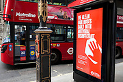 As the UK's Conornavirus pandemic lockdown continues, but with travel restrictions and social distancing rules starting to ease after three months of closures and isolation, a London bus drives past a bus stop where advertising tells the public that buses are being cleaned with antiviral disinfectant, on 9th June 2020, in London, England.