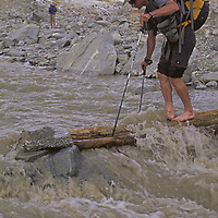 A trekker crosses a crude log bridge over a swollen glacial stream in the Pamir Mountains of Xinjiang, China.
