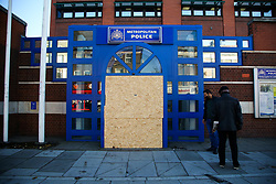 © Licensed to London News Pictures. 12/11/2020. London, UK. People look at the entrance to Edmonton Police Station in north London which is boarded following an incident where a vehicle was driven into the police station just before 7pm on Wednesday, 11 November. A 45-year-old man left the vehicle before attempting to set fire to it using petrol. He was arrested by officers on suspicion of arson and is remanded in custody. The incident is not being treated as terror-related. Photo credit: Dinendra Haria/LNP