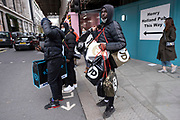 Youngmen who have been out shopping at JD Sports and are laden with many shopping bags as the national lockdown ends and the new three tier system of local coronavirus restrictions begins, shoppers head out to Oxford Street to catch up on shopping as non-essential shops are allowed to reopen on 2nd December 2020 in London, United Kingdom. Many shoppers wear face masks outside on the street as a precaution as there are so many people around.