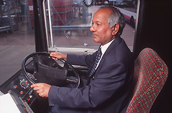 Male bus driver wearing blazer jacket and tie driving double decker bus,