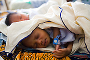 Five-day-old twins lie on a bed in a maternity ward at the La Polylcinic in Accra, Ghana on Tuesday June 16, 2009.
